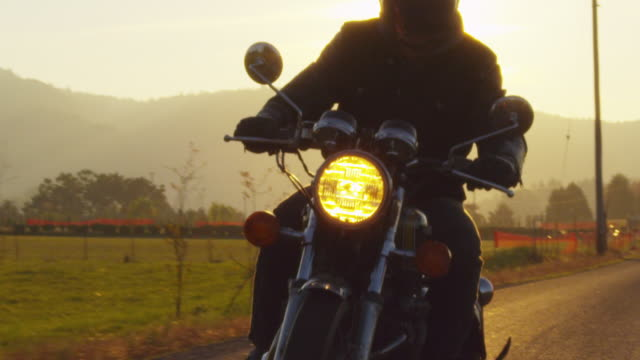 Slow motion of biker riding motorcycle on road during sunset