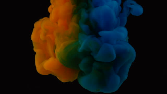slow motion of blue and orange ink flowing into water - orange colour stock videos & royalty-free footage