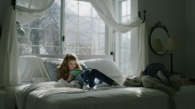 slow motion of boy climbing on bed watching sister reading book near bay window / pleasant grove, utah, united states - bay window stock videos & royalty-free footage