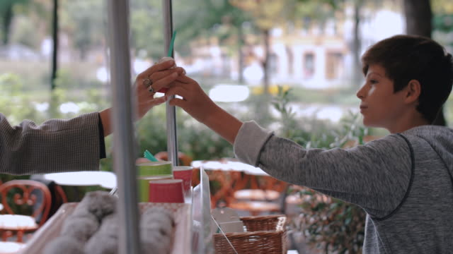 slow motion of boy giving ice cream cup to female customer at stand in city - stockholm stock-videos und b-roll-filmmaterial