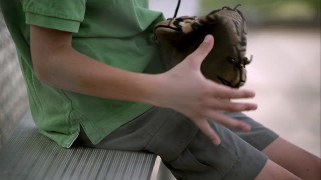 slow motion of boy holding baseball mitt then setting it down next to him on bench. - mittlerer teil stock-videos und b-roll-filmmaterial