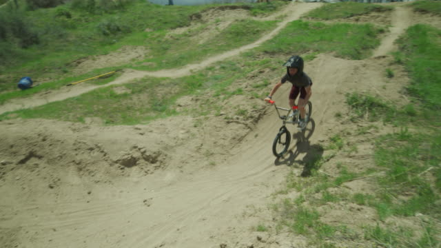 slow motion of boy jumping hill and twisting midair on bicycle at bike park / salt lake city, utah, united states - bmx stock-videos und b-roll-filmmaterial