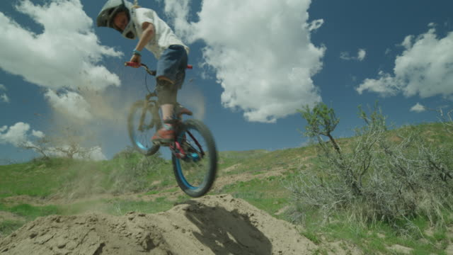 slow motion of boy jumping hill on bicycle at bike park and falling / salt lake city, utah, united states - twisted stock videos & royalty-free footage