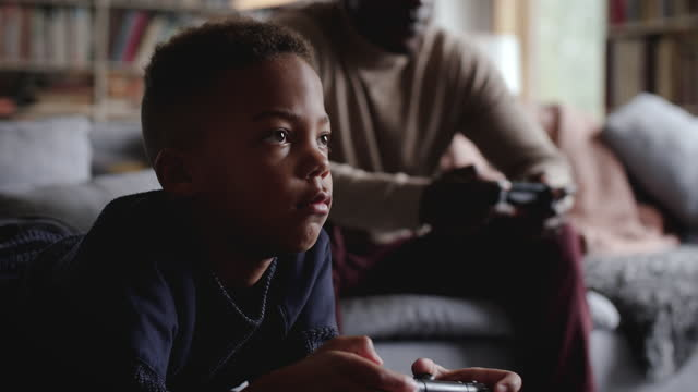 slow motion of boy playing video game with father in living room at home - shaky stock videos & royalty-free footage