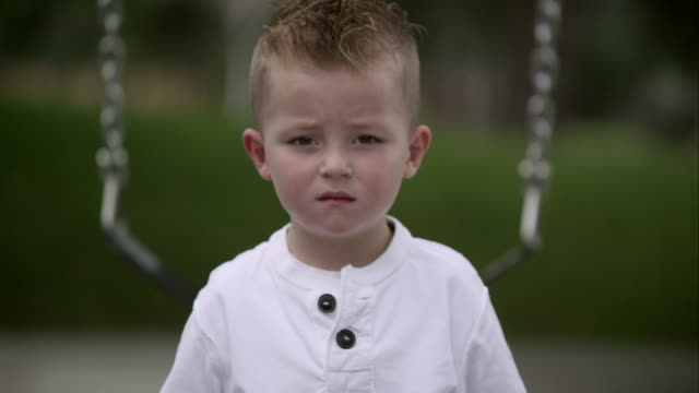 Slow motion of boy standing in front of swing with blank look on face.