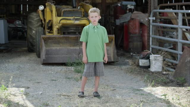 slow motion of boy with cleft lip standing in front of tractor. - korta ärmar bildbanksvideor och videomaterial från bakom kulisserna