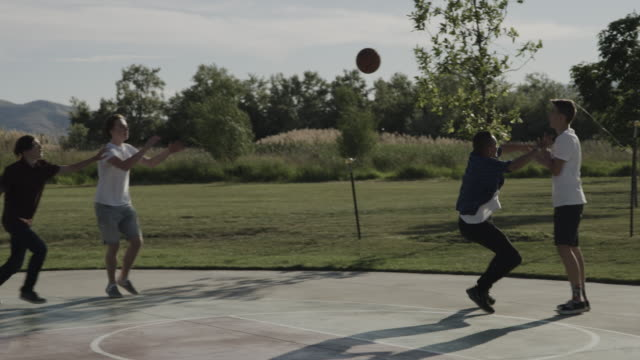 vídeos de stock e filmes b-roll de slow motion of boys playing basketball on court in park / lehi, utah, united states - lehi