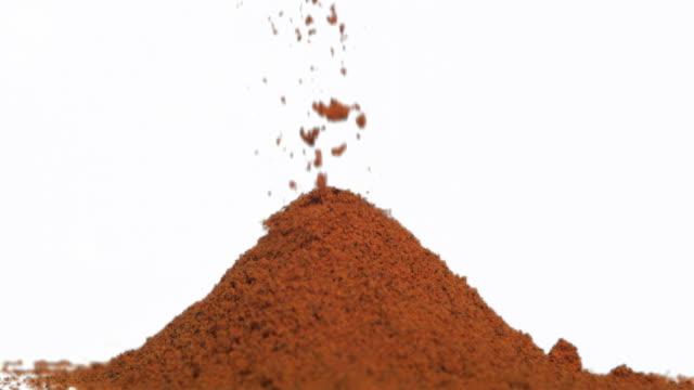 Slow motion of brown powder falling onto a heap