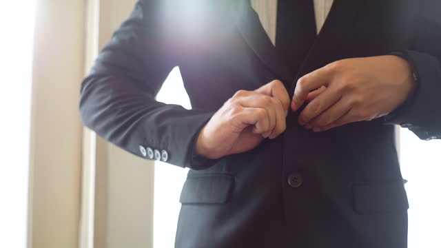 slow motion of businessman in suit fastening button in the room - formalwear stock videos & royalty-free footage