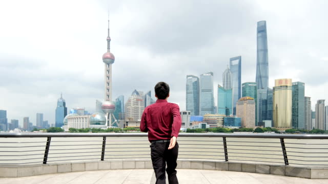 slow motion of businessman running against shanghai skyline - standing stock videos & royalty-free footage