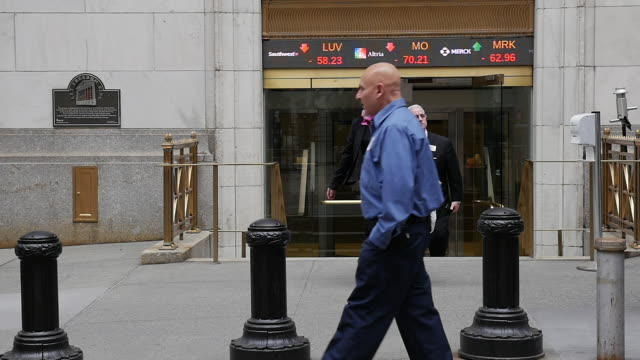 Slow motion of businessmen walking in front of New York stock exchange building.