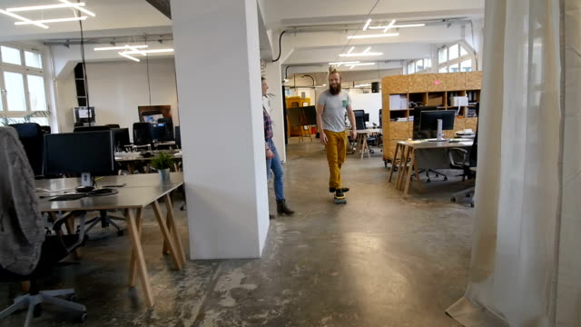 Slow motion of businesswoman looking at colleague skateboarding