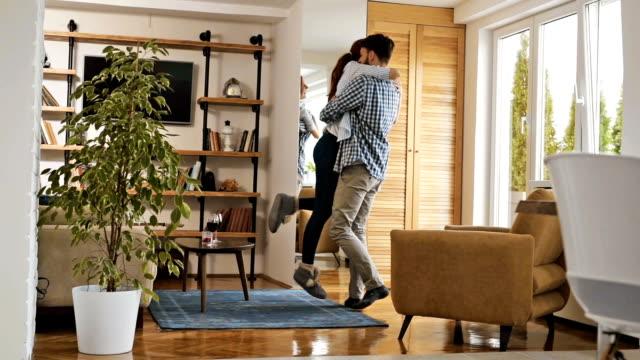 slow-motion von unbeschwerten liebespaar spinnen im wohnzimmer. - full length stock-videos und b-roll-filmmaterial