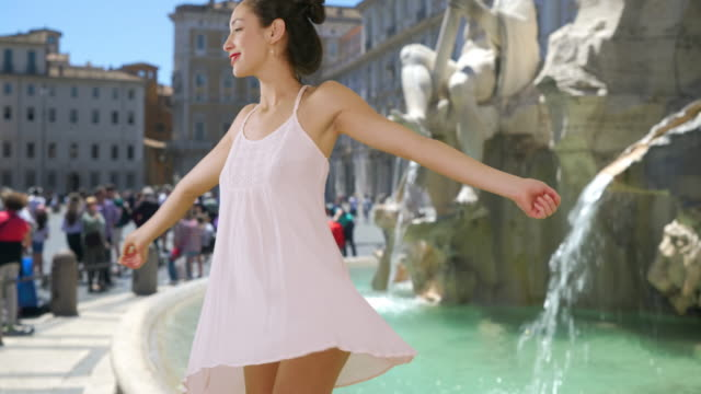 Slow motion of carefree Latina woman twirling in sundress by fountain in Rome