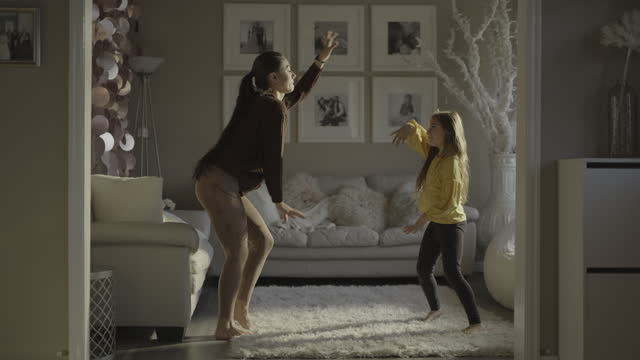 slow motion of carefree mother and daughter dancing in livingroom / south jordan, utah, united states - adult stock videos & royalty-free footage