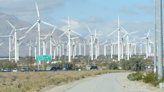 vídeos de stock e filmes b-roll de slow motion of cars and semi-trucks moving past a wind farm. travel restrictions have been loosened following the wide spread vaccination in america,... - outdoor pursuit
