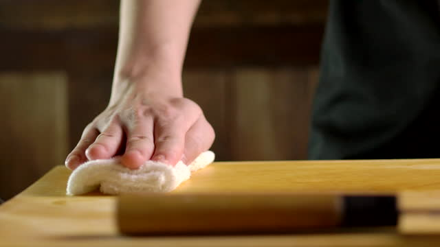 slow motion of chef cleaning chopping board by wiping - chopping board stock videos & royalty-free footage