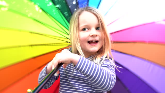 slow motion of child twirling colourful umbrella - spectrum stock videos & royalty-free footage