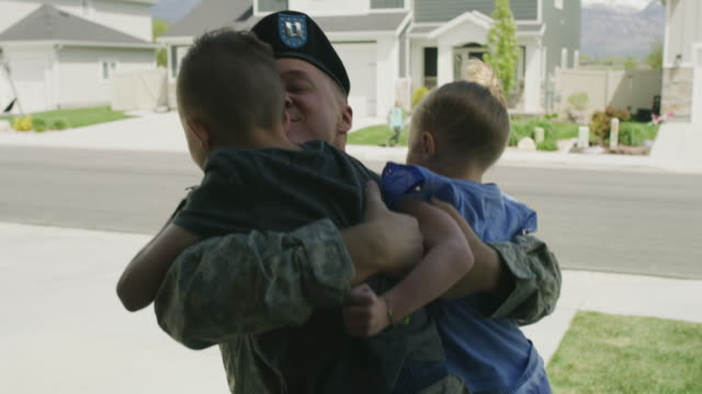 slow motion of children hugging and kissing soldier father returning home from duty / lehi, utah, united states - lehi stock videos & royalty-free footage