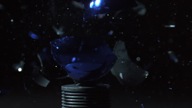 Slow motion of christmas ornament shattering.