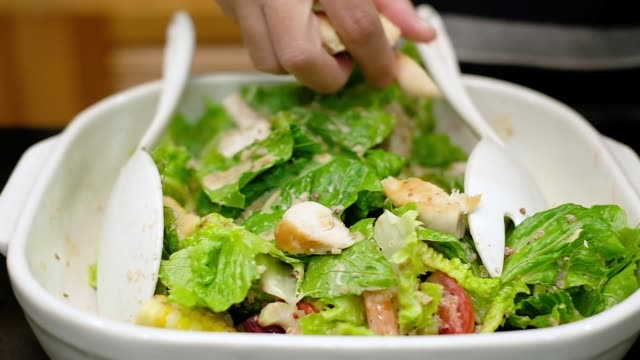slow motion of close up  hand put roasted chicken on vegetable salad in white bowl