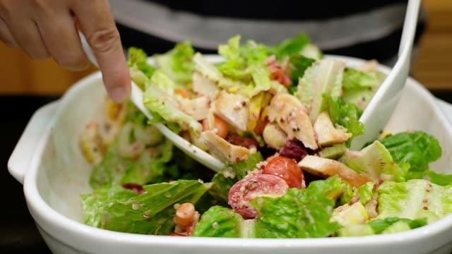 手をクローズ アップのスローモーションを使用して、白いスプーンで新鮮な鶏のサラダとドレッシングのサラダを混合します。 - dieting点の映像素材/bロール