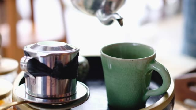 slow motion of close up pouring tea into green coffee mug with tea pot - tea pot stock videos and b-roll footage