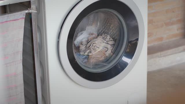 vidéos et rushes de ralenti des vêtements lavant tournant dans la machine à laver dans le coup de ralenti. porte de machine à laver avec des vêtements rotatifs à l'intérieur. - un seul objet