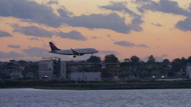 slow motion of commercial plane landing in laguardia airport in new york city at twilight - delta stock videos and b-roll footage