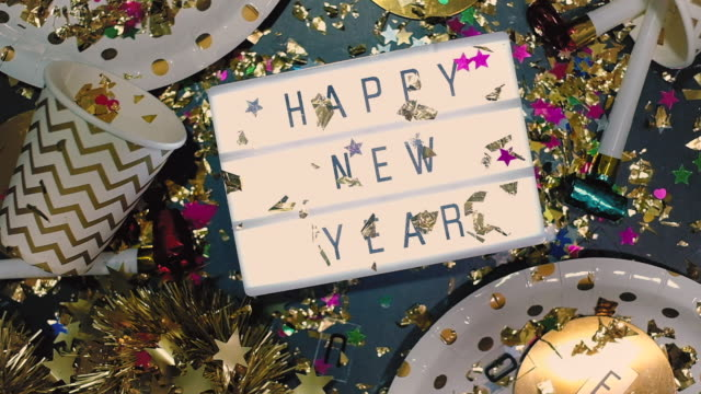 slow motion of confetti falling down to happy new year ligthbox with party cup,party blower,tinsel.holiday celebration table top view. - tinsel stock videos & royalty-free footage