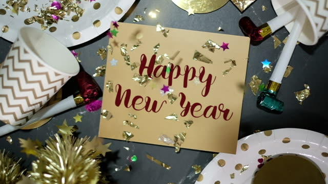 slow motion of confetti falling down to happy new year on golden greeting card with party cup,party blower,tinsel.holiday celebration table top view - flat lay stock videos & royalty-free footage