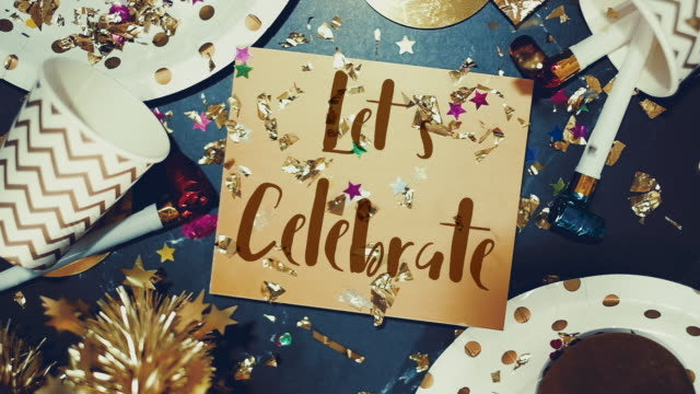 Slow motion of confetti falling down to Let's belebrate on golden greeting card with party cup,party blower,tinsel.holiday celebration table top view