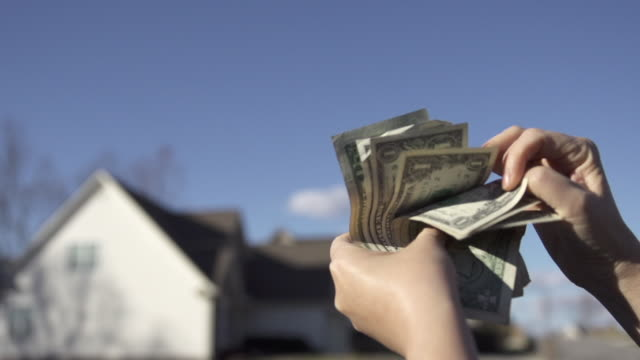 Slow Motion of Counting US Dollar Money in Front of Blurred Homes