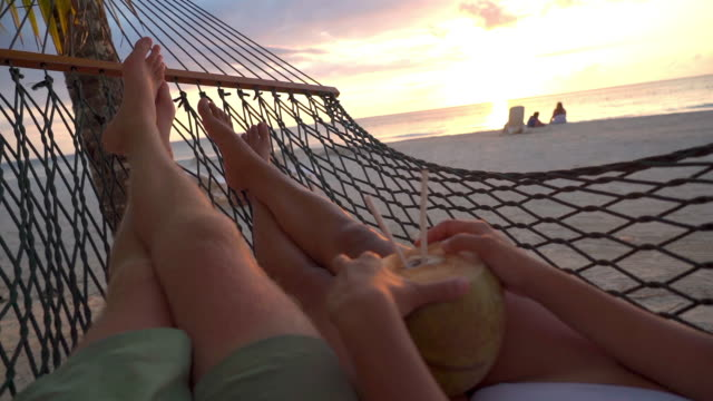 slow motion of couple lying with coconut on hammock at beach, tourists relaxing against sky during sunset - montego bay, jamaica - hammock stock videos & royalty-free footage