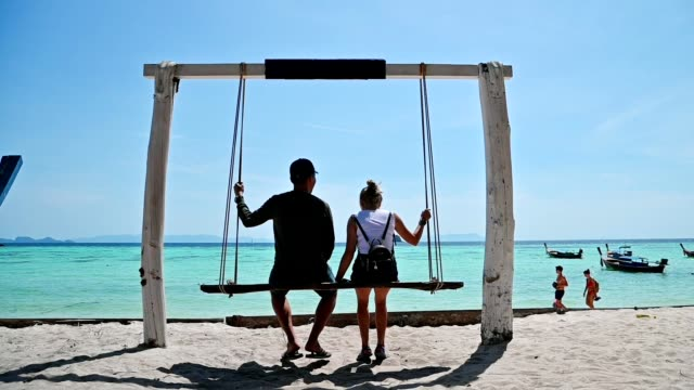 slow motion of couple sitting on wooden swing on the beach in tropical sea at lipe island - tropical climate stock videos & royalty-free footage