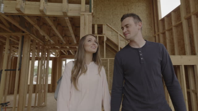 slow motion of couple walking and pointing in interior of home under construction / pleasant grove, utah, united states - construction frame stock videos & royalty-free footage