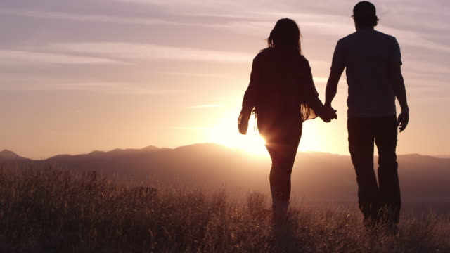 Slow motion of couple walking on hill top towards sunset as they turn and kiss