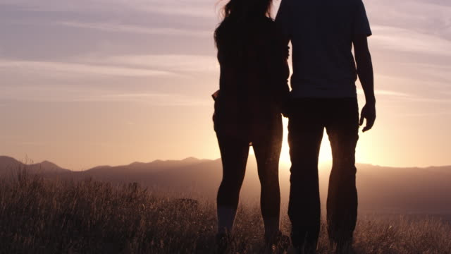 vidéos et rushes de slow motion of couple walking on hill top towards sunset as they turn and kiss - embrasser sur la bouche