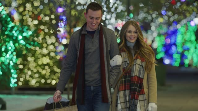 slow motion of couple walking on sidewalk during christmas carrying shopping bags / provo, utah, united states - provo stock videos & royalty-free footage