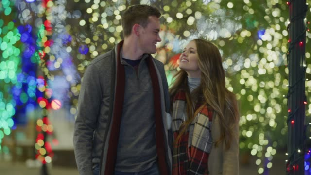 stockvideo's en b-roll-footage met slow motion of couple walking outdoors and kissing during christmas / provo, utah, united states - provo