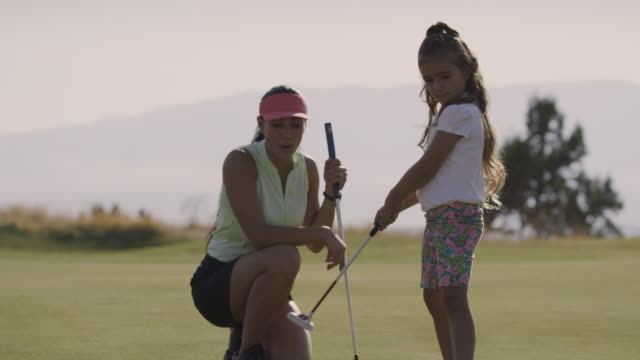slow motion of crouching woman golfer teaching putting to girl then high-fiving / cedar hills, utah, united states - daughter stock videos & royalty-free footage