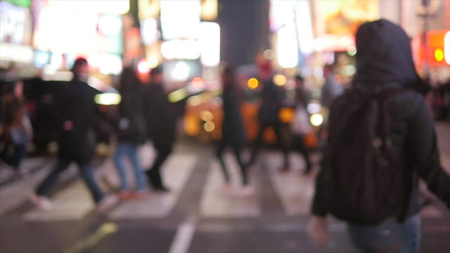 vídeos de stock, filmes e b-roll de slow motion of crowd of people walking in city at night. pedestrians crossing street - foco difuso