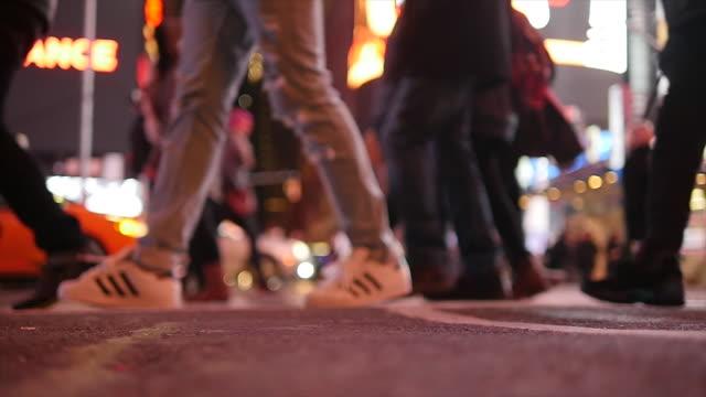 slow motion of crowd of people walking in city at night. pedestrians crossing street - ソフトフォーカス点の映像素材/bロール