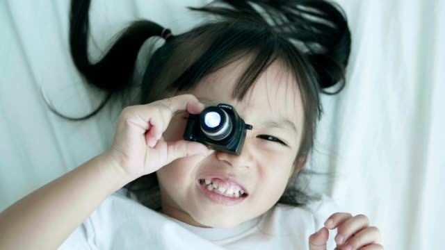 Slow motion of cute baby girl playing camera with positive emotion in the bed on weekend