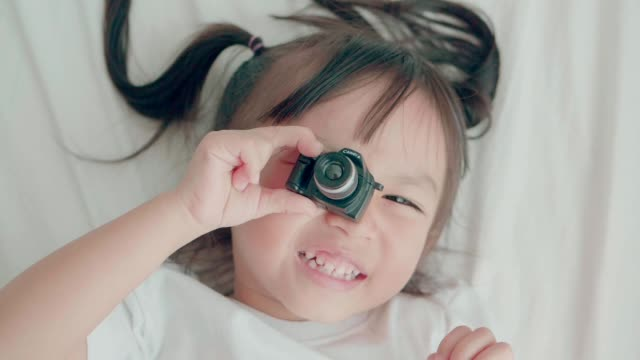 Slow motion of cute baby girl playing camera with positive emotion on weekend