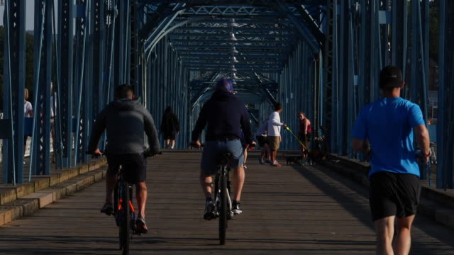 slow motion of cyclists and jogger crossing the bridge in chattanooga, tn - chattanooga stock videos and b-roll footage
