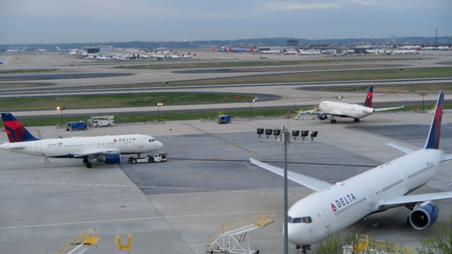 stockvideo's en b-roll-footage met slow motion of delta plan taxiing at the atlanta international airport - broek