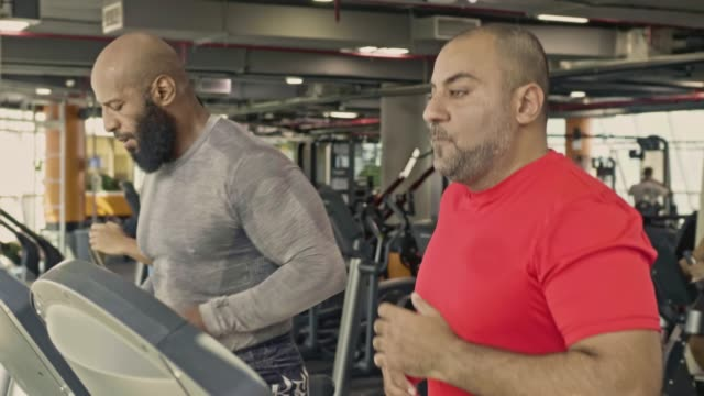 slow motion of determined diverse mature men running on treadmill in gym - mature men stock videos & royalty-free footage
