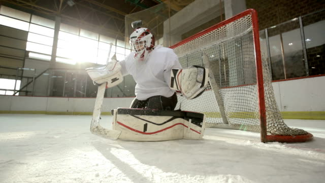 Slow motion of determined ice hockey goaltender defending his goal at the arena.
