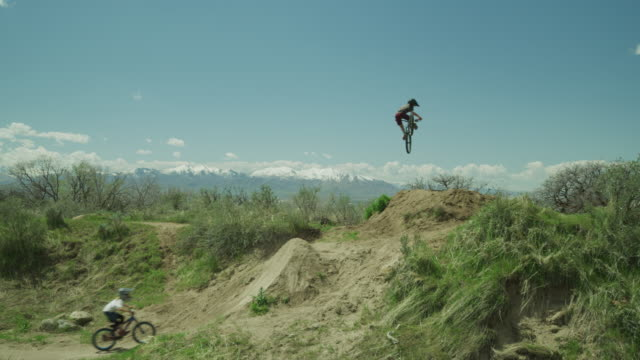 slow motion of distant boys jumping hill on bicycles at bike park / salt lake city, utah, united states - twisted stock videos & royalty-free footage